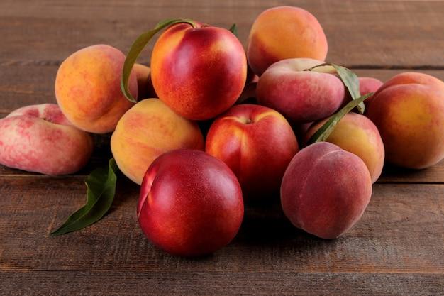 Zusammensetzung vieler pfirsichsorten auf einem braunen holztisch. früchte.