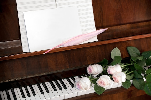 Zusammensetzung von den hellrosa rosen, vom musikalischen papier und vom weißen leerbeleg mit rosa spulefeder auf braunem klavier.