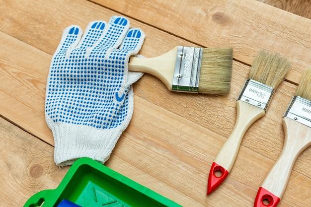Zusammensetzung von den malwerkzeugen mit pinseln, handschuhen und farbenrolle auf dem hölzernen hintergrund