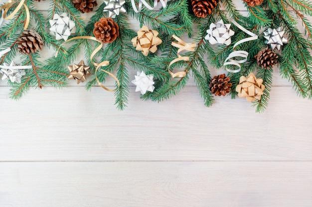 Zusammensetzung von den niederlassungen eines weihnachtsbaums, der kegel, der dekorativen bänder und der bögen.