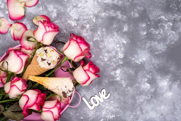 Zusammensetzung von eiscremewaffeln mit rosenblumensträußen auf einem steinhintergrund