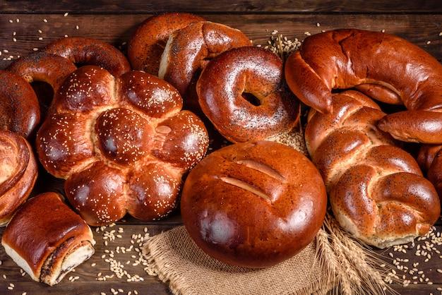 Zusammensetzung von frisch gebackenen süßen brötchen mit mohn und marmelade. süßes backen als komposition auf einem holztisch ausgelegt