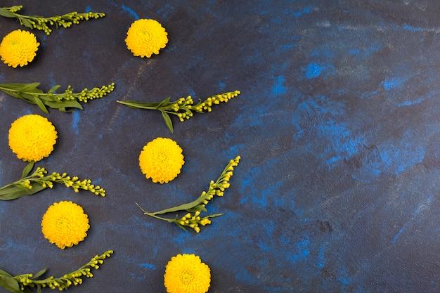 Zusammensetzung von frischen gelben blumen und von grünen blättern