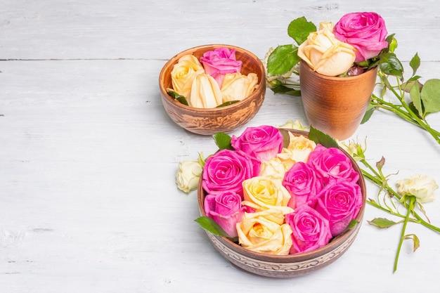 Zusammensetzung von frischen mehrfarbigen rosen im küchengerät. das festliche konzept für hochzeiten, geburtstage, 8. märz, mutter- oder valentinstag. grußkarte, flach, alter holztisch
