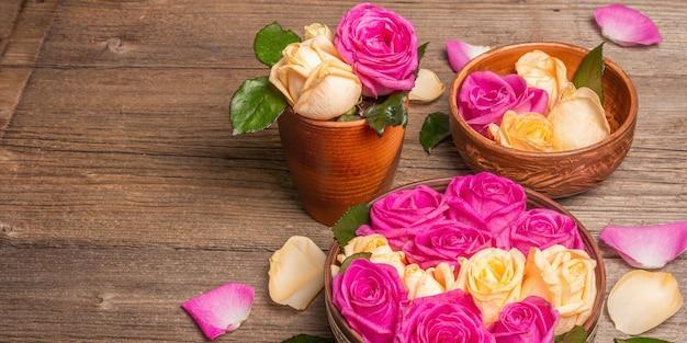 Zusammensetzung von frischen mehrfarbigen rosen im küchengerät. das festliche konzept für hochzeiten, geburtstage, 8. märz, mutter- oder valentinstag. grußkarte, flach, vintage-holztisch, banner