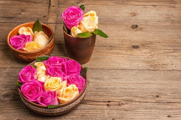 Zusammensetzung von frischen mehrfarbigen rosen im küchengerät. das festliche konzept für hochzeiten, geburtstage, 8. märz, mutter- oder valentinstag. grußkarte, flach, vintage-holztisch