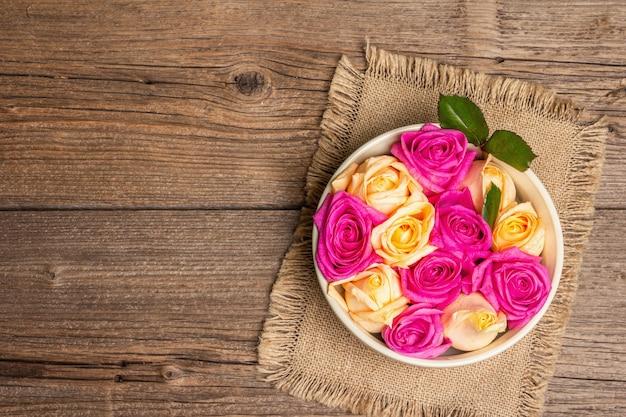 Zusammensetzung von frischen mehrfarbigen rosen in keramikschale. das festliche konzept für hochzeiten, geburtstage, 8. märz, mutter- oder valentinstag. grußkarte, flach, vintage-holztisch