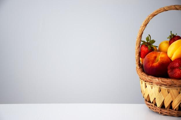 Zusammensetzung von frischen reifen saftigen früchten und beeren: pfirsiche, erdbeeren und aprikosen im weidenkorb