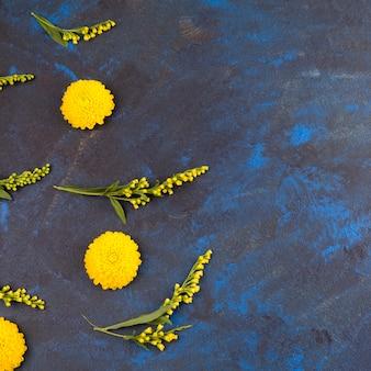 Zusammensetzung von gelben blumen und von grünen blättern