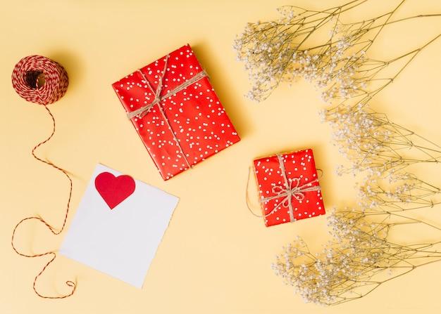 Zusammensetzung von geschenkkartons, ornament herz auf papier, pflanzen und fäden