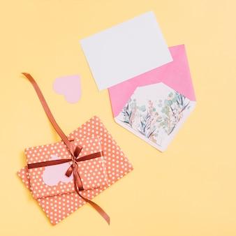 Zusammensetzung von geschenkkartons, ornament herzen, papier und umschlag