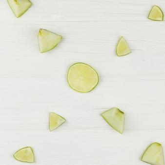 Zusammensetzung von geschnittenen äpfeln und von kalk auf weißem hintergrund