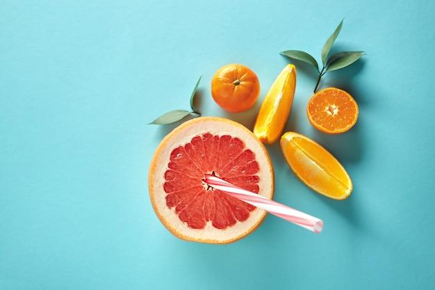 Zusammensetzung von grapefruit, mandarine und orangenstücken mit blättern auf einer draufsicht des blauen papierhintergrundes. das konzept eines vitamingetränks. platz kopieren