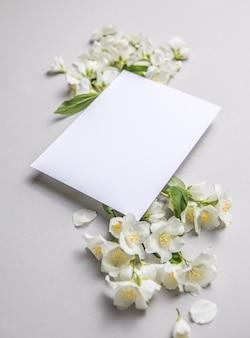 Zusammensetzung von grünen blättern und blüten von jasmin mit einem leeren blatt für text auf grauem papierhintergrund. natürliches layout für postkarte. flache lage