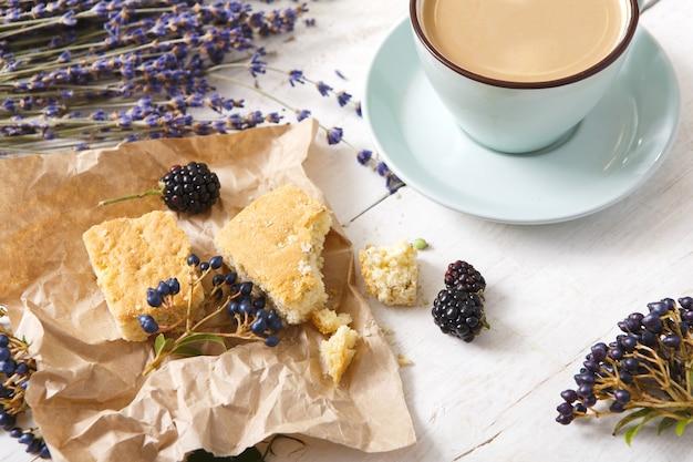 Zusammensetzung von kaffee, keksen, beeren und lavendelblumen, nahaufnahme auf weißem holz. blaue tasse mit cremigem schaum