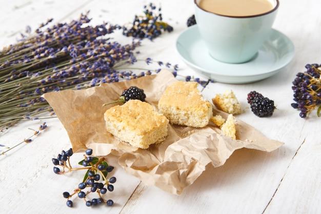 Zusammensetzung von kaffee, keksen, beeren und lavendelblumen, nahaufnahme auf weißem holz.