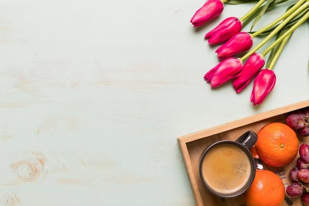 Zusammensetzung von kaffee und früchten mit tulpen
