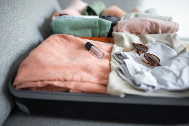 Zusammensetzung von kleidung und accessoires in einem koffer