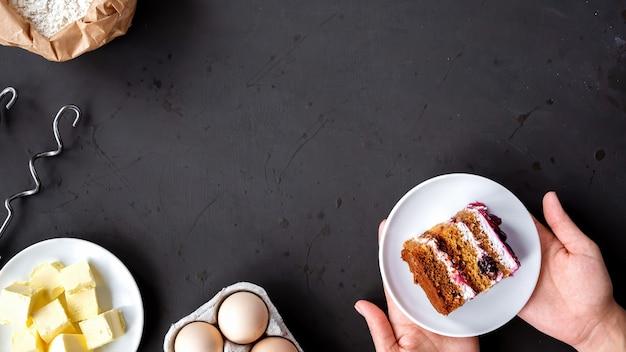 Zusammensetzung von kochgeräten und zutaten, weibliche hände, die einen kuchen halten, dunkler hintergrund