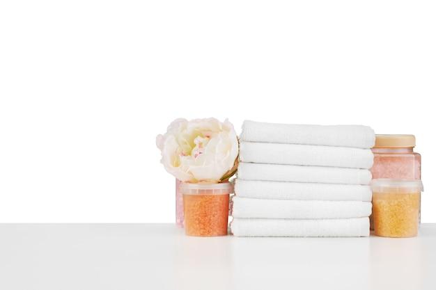 Zusammensetzung von kosmetikflaschen und handtüchern auf weißem hintergrund