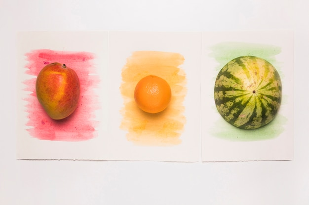 Zusammensetzung von leckeren ganzen mischfrüchten auf mehrfarbiger aquarelloberfläche