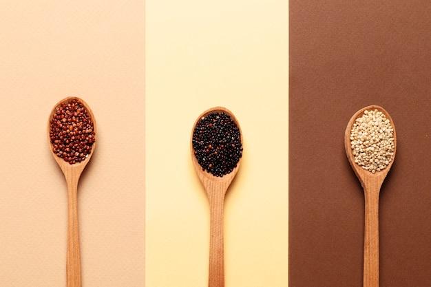 Zusammensetzung von quinoa aller art in holzlöffeln im hintergrund. ansicht von oben.