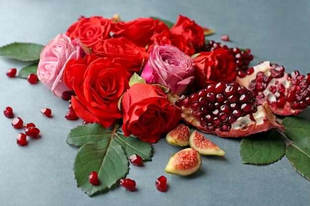 Zusammensetzung von rosen, granatapfelstücken und feigen auf farbe
