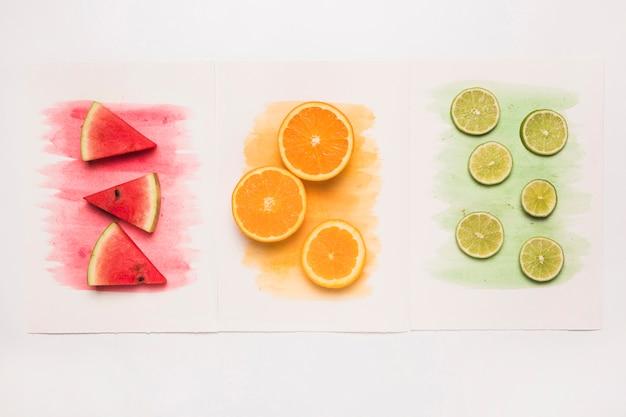 Zusammensetzung von saftigen schnittfrüchten auf farbigem aquarellspritzen