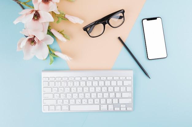 Zusammensetzung von smartphone, tastatur, brille, blumen und bleistift