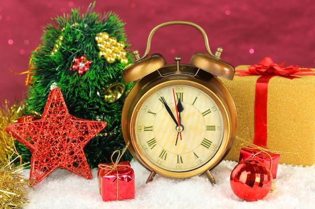 Zusammensetzung von uhr und weihnachtsschmuck auf hellem hintergrund