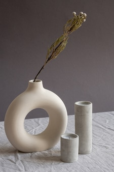 Zusammensetzung von zwei aromatisch ausgeblasenen kerzen in weißen keramikgläsern, die auf tisch durch kreative handgemachte vase mit getrockneten blumen stehen
