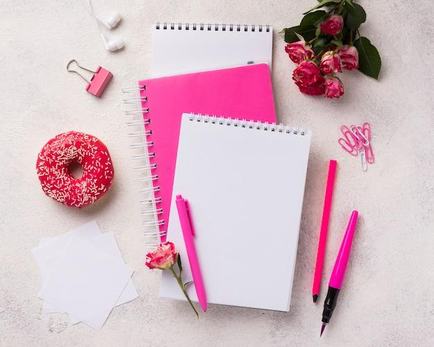 Zusammenstellung auf notizbüchern mit krapfen und blumenstrauß von rosen