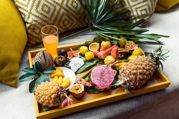 Zusammenstellung der tropischen früchte und frischer saft auf einem gelben behälter mit palmblatt. ansicht von oben. frühstück