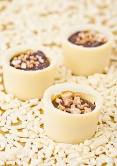 Zusammenstellung der weißen pralinenluxusvielfalt auf einem goldenen hintergrund mit weißen schokoladenstücken