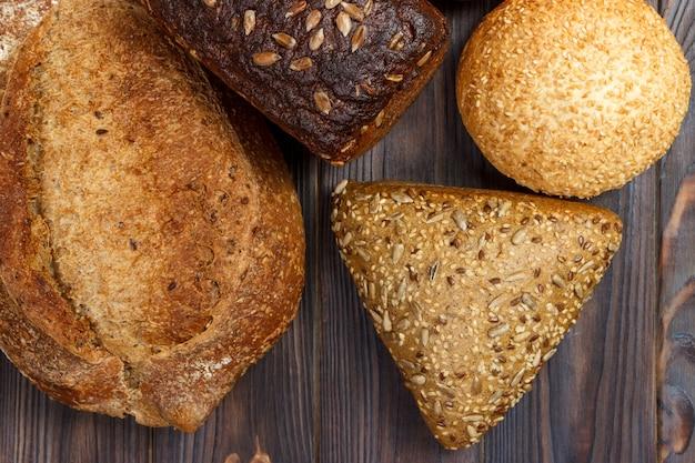 Zusammenstellung des gebackenen brotes auf dunklem hölzernem hintergrund. bäckerei und lebensmittelgeschäftkonzept. wohnung lag mit platz für text