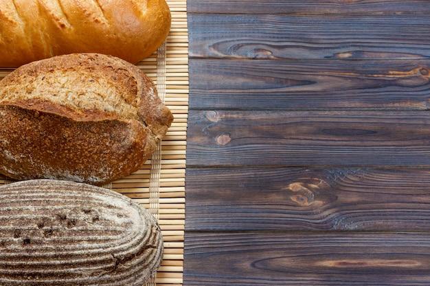 Zusammenstellung des gebackenen brotes auf hölzerner tabelle. draufsicht mit kopienraum
