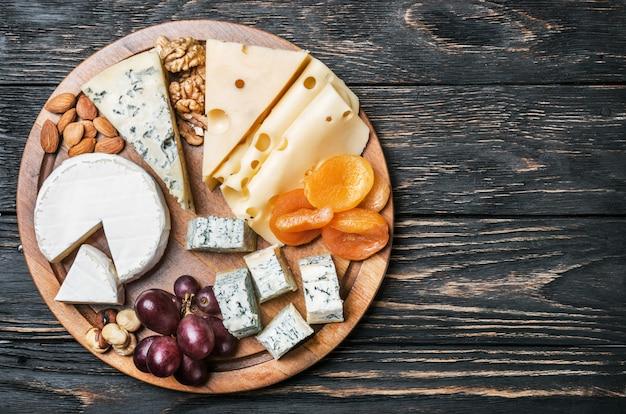 Zusammenstellung des käses mit früchten und trauben auf einem holztisch
