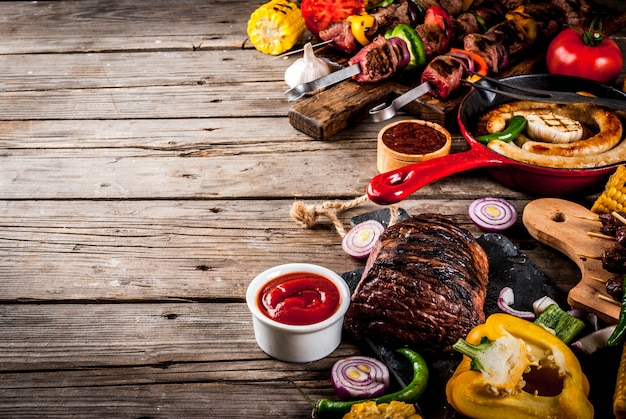 Zusammenstellung verschiedenes grillnahrungsmittelgrillfleisch, grillpartyfest - schaschlik, würste, gegrilltes fleischfilet, frisches gemüse, soßen, gewürze, auf alter hölzerner rustikaler tabelle, über kopienraum