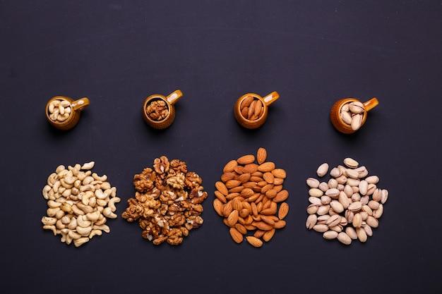 Zusammenstellung von nüssen auf einem schwarzen schiefer - gesunder snack.