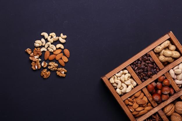 Zusammenstellung von nüssen in einer holzkiste auf einem schwarzen schiefer - gesunder snack.