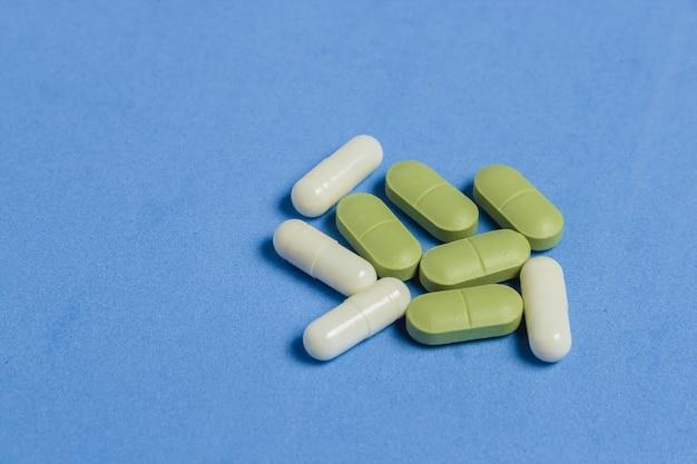 Zusammenstellung von pillen, von tabletten und von kapseln auf blauer tabelle.
