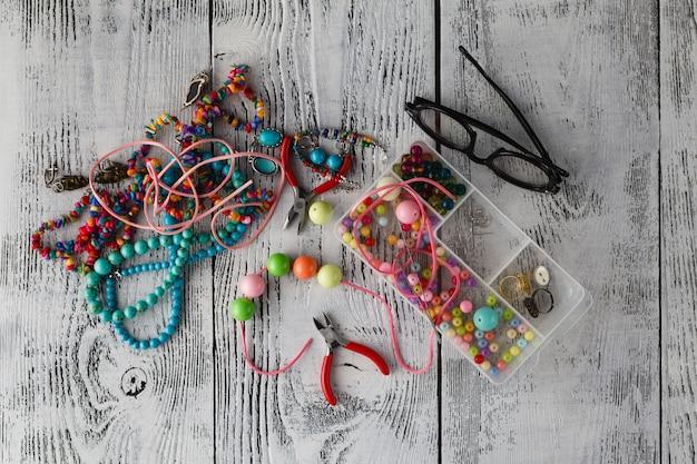 Zusammenstellung von schmuck aus fimo im böhmischen stil mit schachtel mit kleinen perlen. hobby, handwerk. zange mit unfertiger halskette.