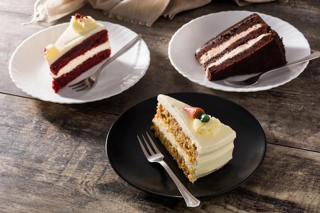 Zusammenstellung von süßen kuchenscheiben schokoladen-karotten- und samtkuchenscheiben auf holztisch