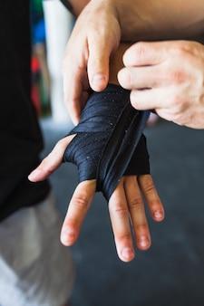 Zuschneiden sie sportler, die hand mit elastischem band aufnehmen