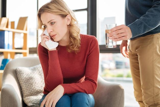 Zustand der depression. unglückliche launische junge frau, die ein papiertaschentuch hält und sich traurig fühlt, während sie in einem zustand der depression ist