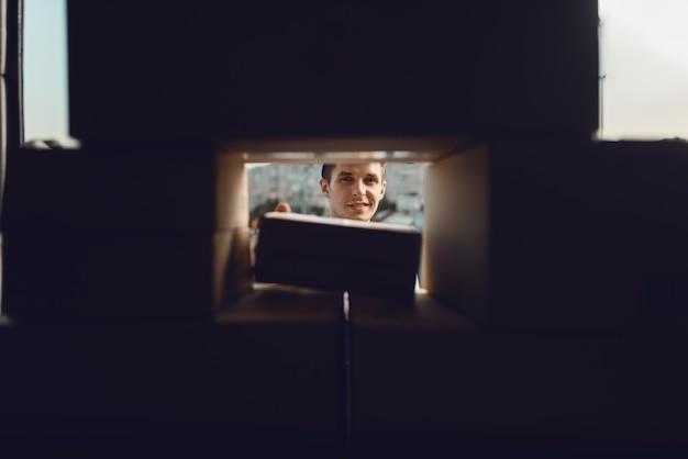 Zusteller, der durch einen riss in den kisten mit paketen schaut, lieferservice.