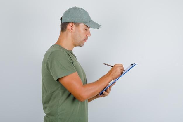 Zusteller, der notizen auf zwischenablage im armeegrünen t-shirt, in der kappe und im beschäftigten blick nimmt.