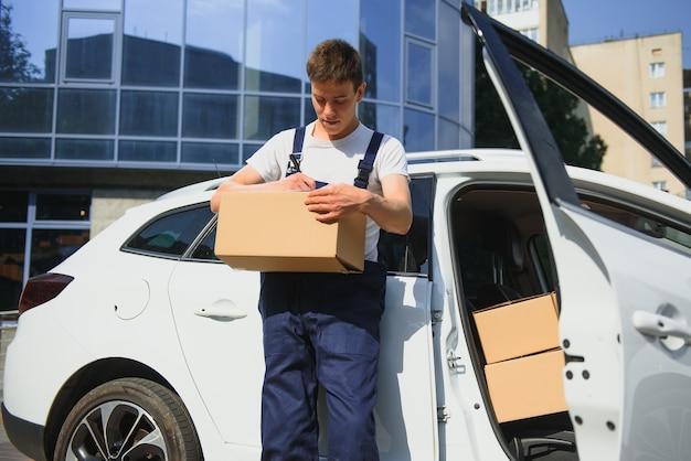 Zusteller hält pakete am auto und liefert