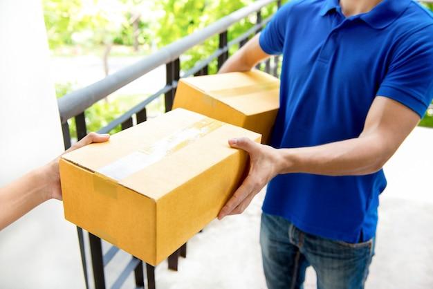 Zusteller in blauer uniform, die paketbox zum empfänger übergibt