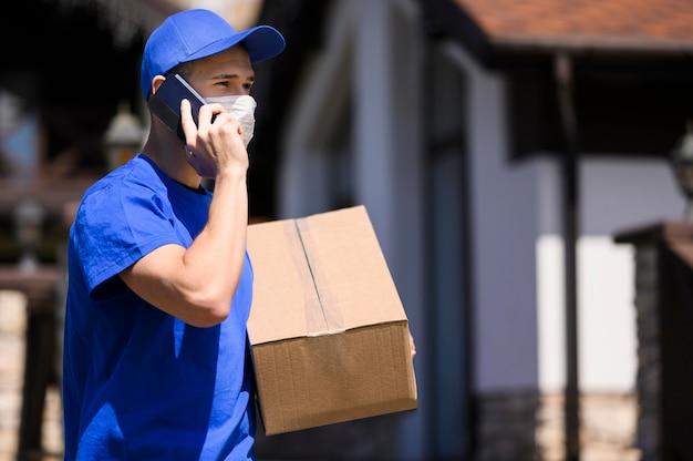 Zusteller mit gesichtsmaske, die paket trägt